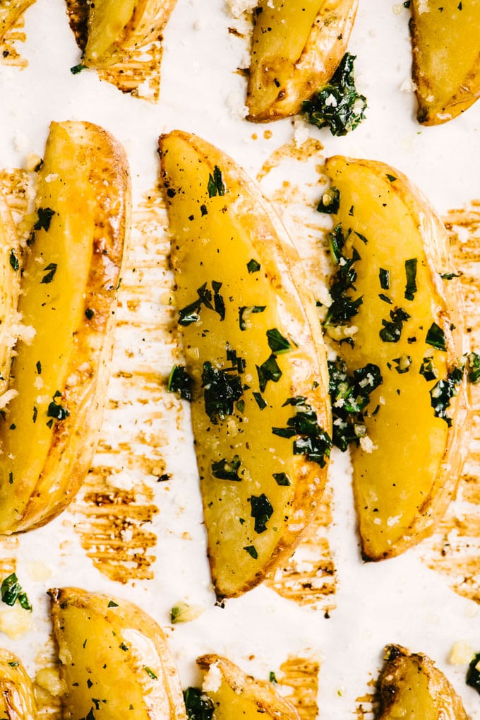 Crispy oven baked potato wedges on a baking sheet brushed with basil butter and sprinkled with parmesan cheese.