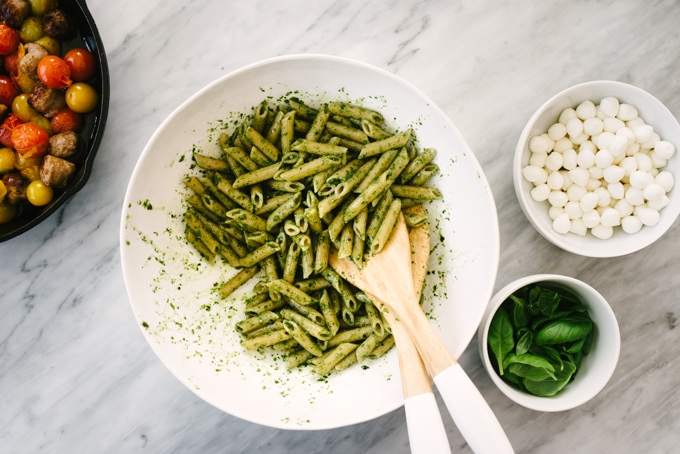 A large white pasta bowl filled with whole wheat penne tossed with basil pesto. Small bowls of fresh mozzarella and fresh basil are on the side, along with a skillet filled with burst tomatoes and Italian sausage.