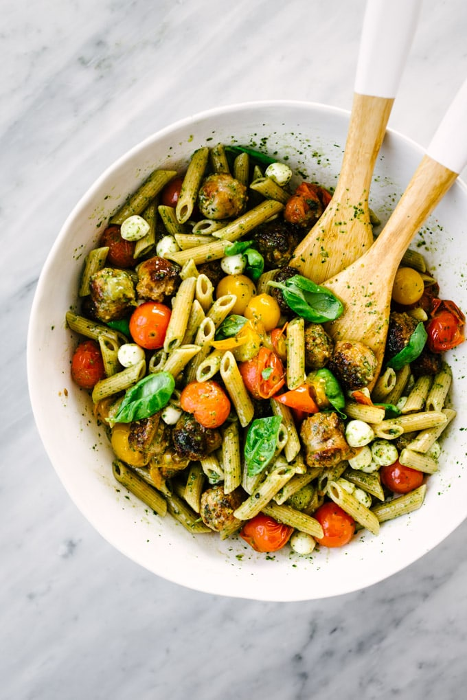 A large white pasta bowl filled with freshly tossed summer caprese pasta with italian sausage and clean basil pesto resting on a marble table.