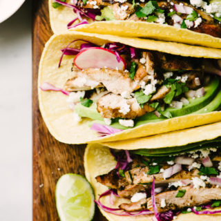 Easy cilantro lime grilled chicken tacos in corn tortillas with avocado on a wood cutting board.