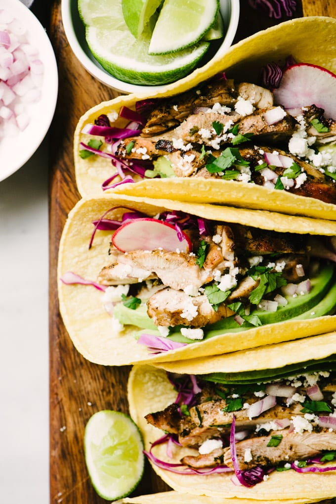 Four grilled chicken tacos on a cutting board stuffed with cilantro lime chicken, avocado, red cabbage, queso fresco, and radishes.