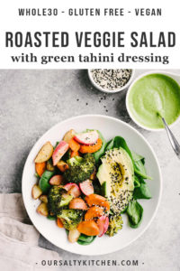 Roasted vegetable salad with avocado, spinach, and sesame seeds and a side of green tahini dressing.