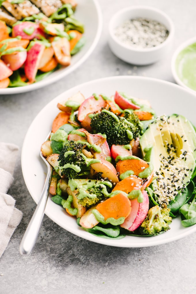 A bowl of roasted vegetables over spinach salad served with half an avocado sprinkled with sesame seeds and drizzled with green tahini dressing.