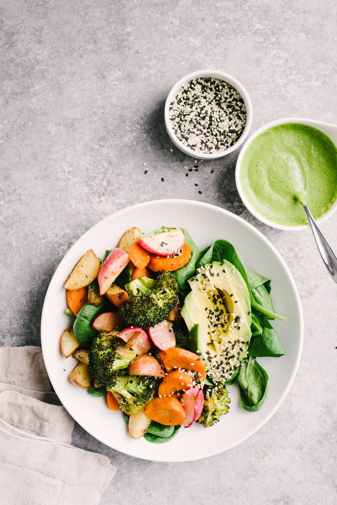 An overhead view of a roasted vegetable salad served with half an avocado, sesame seeds, and a side dish of green tahini sauce on a concrete table.