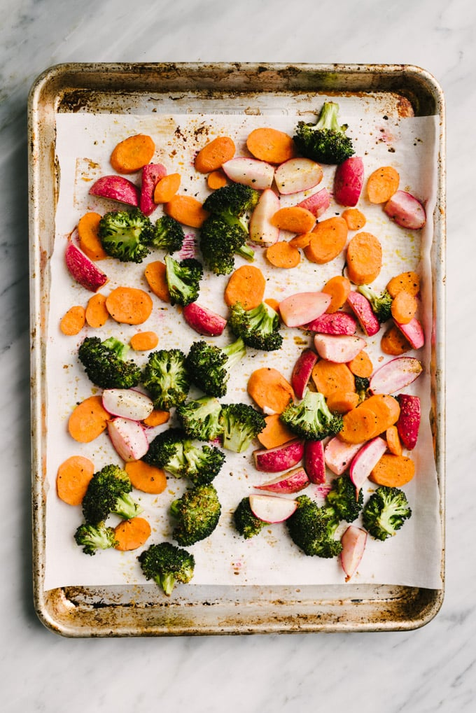 Broccoli florets, quartered radishes, and sliced carrots tossed with olive oil and spices on a parchment lined baking sheet.