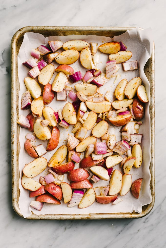 Quartered potatoes and diced red onion tossed with olive oil and spices on a parchment lined baking sheet.