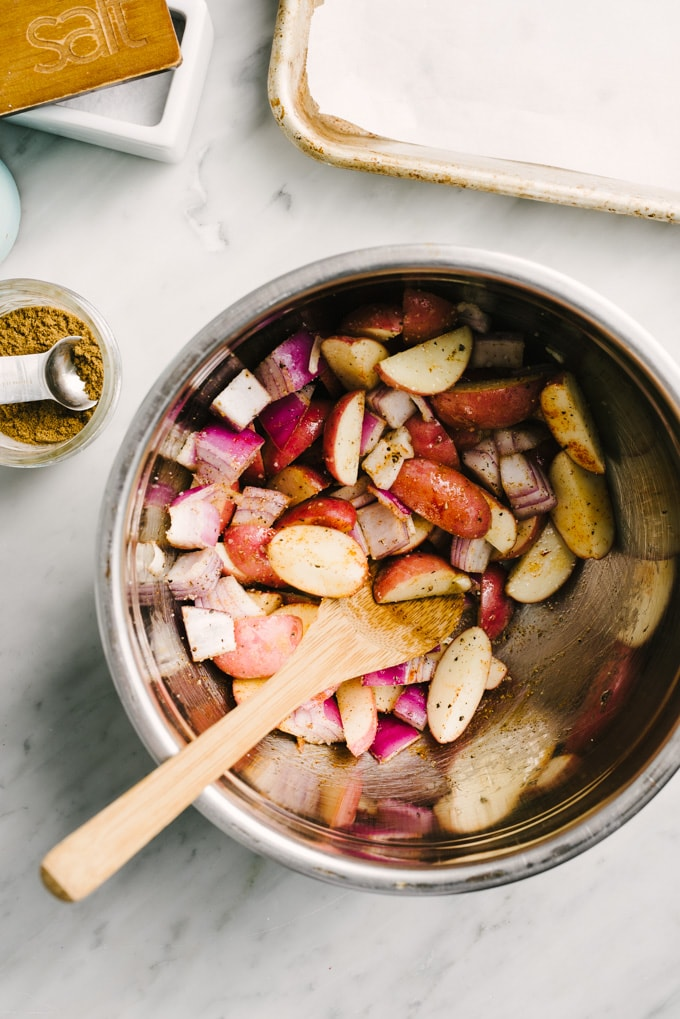 Quartered potatoes and diced red onion in a mixing bowl tossed with olive oil and seasonings.