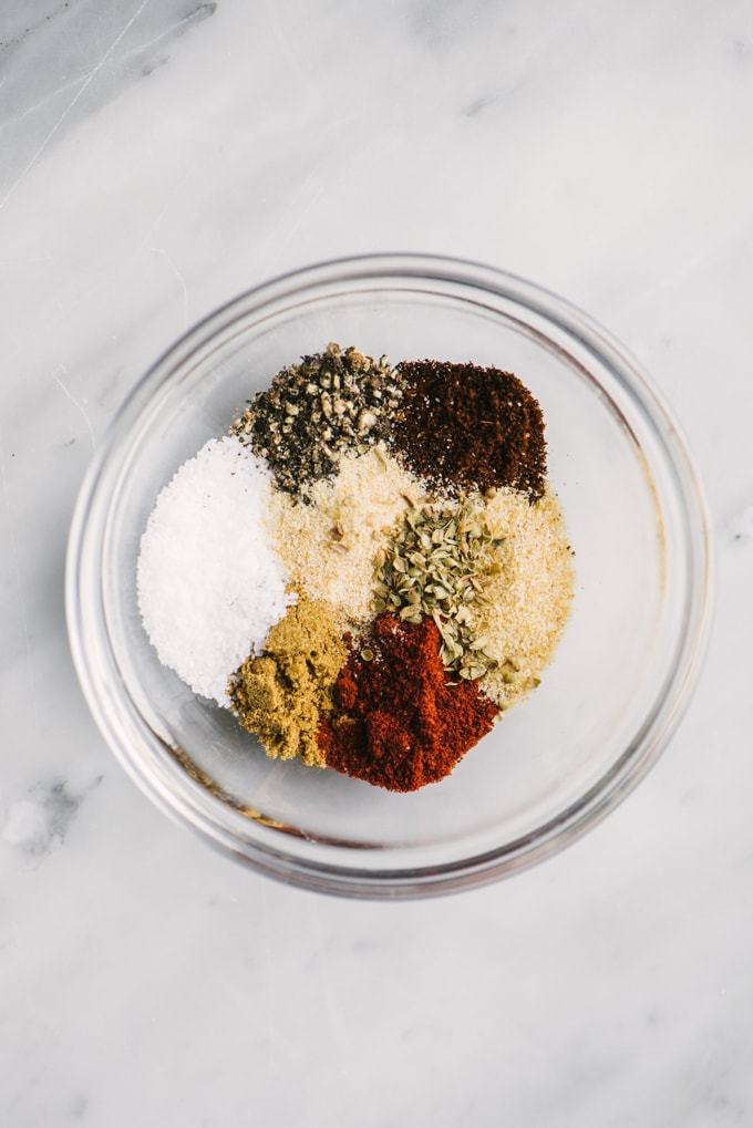 A small glass ramekin filled with steak fajita dry rub seasoning made with cumin, paprika, salt, pepper, chili powder, onion powder, garlic powder, and oregano.