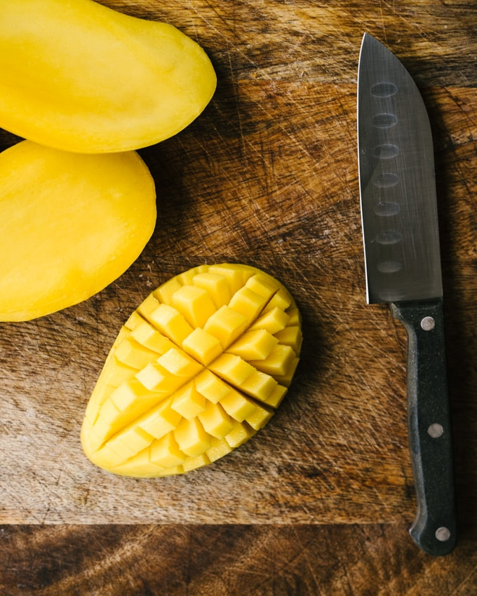 A champagne mango on a cutting board, ready to be diced and added to summer black bean salsa.
