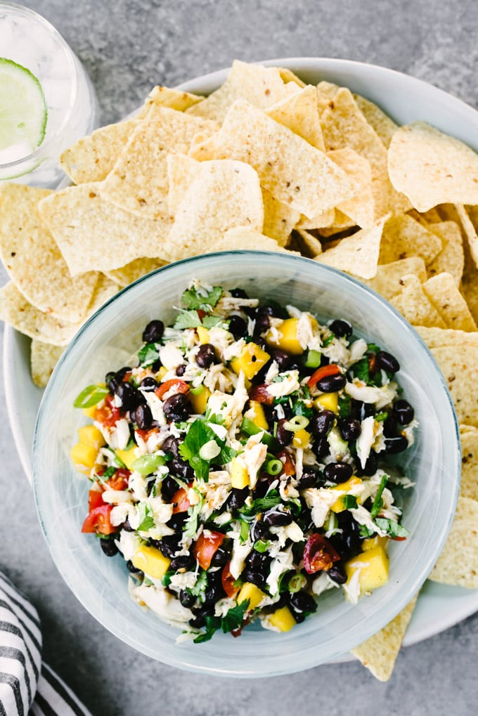 A blue bowl filled with healthy summer salsa made with lump crab meat, mango, and black beans on a platter with yellow corn tortilla chips.