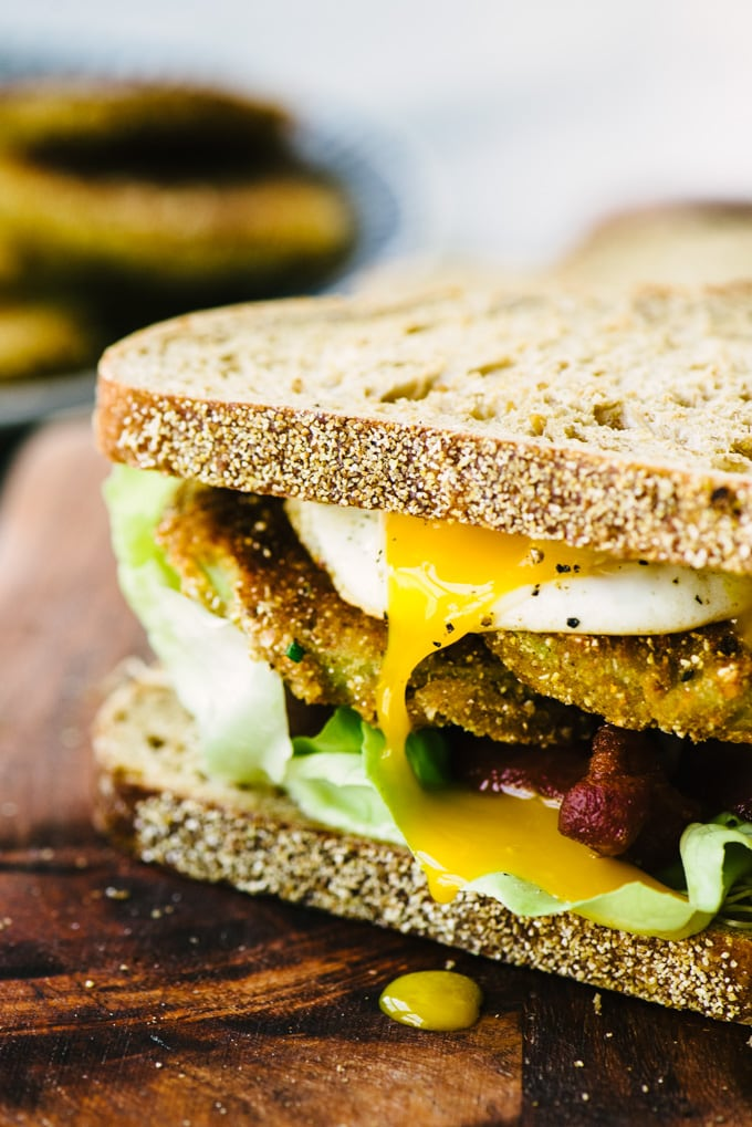 A fried green tomato BLT sandwich on whole grain bread with a fried egg on a wood cutting board.