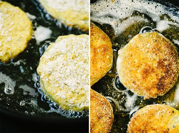 Battered gluten free fried green tomatoes sautéing in olive oil in a cast iron skillet.