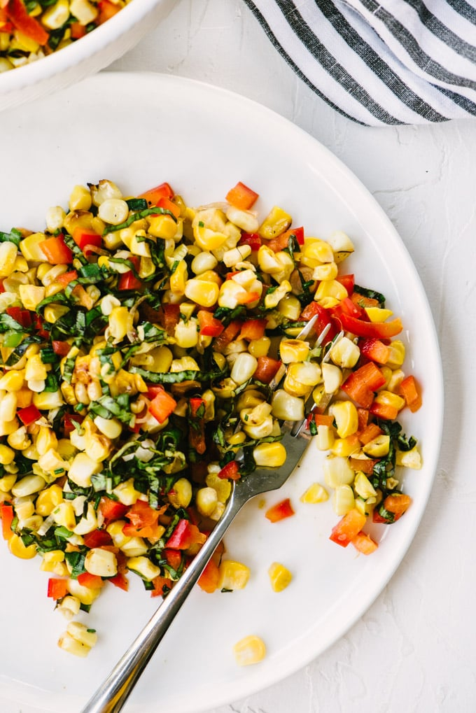A plate with a serving of grilled corn salad with basil, bell peppers, and lime dressing.