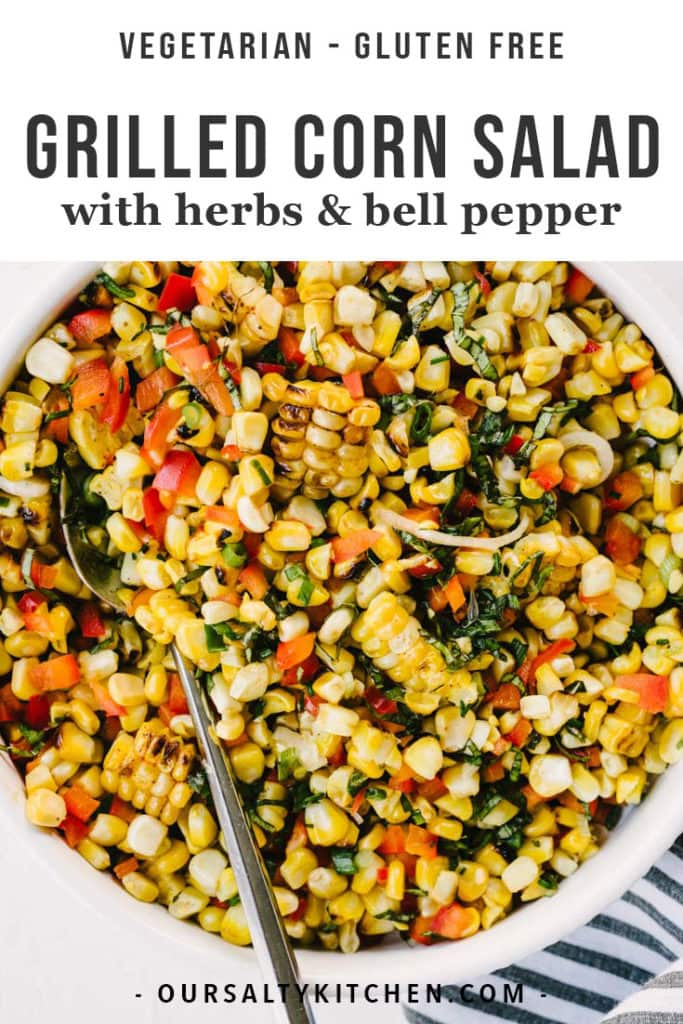 A bowl of grilled corn salad with herbs and bell peppers.