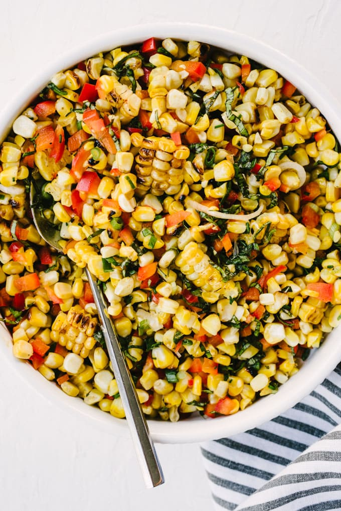 A bowl of grilled sweet corn summer salad with red bell pepper, basil, and green onions and lime honey dressing.