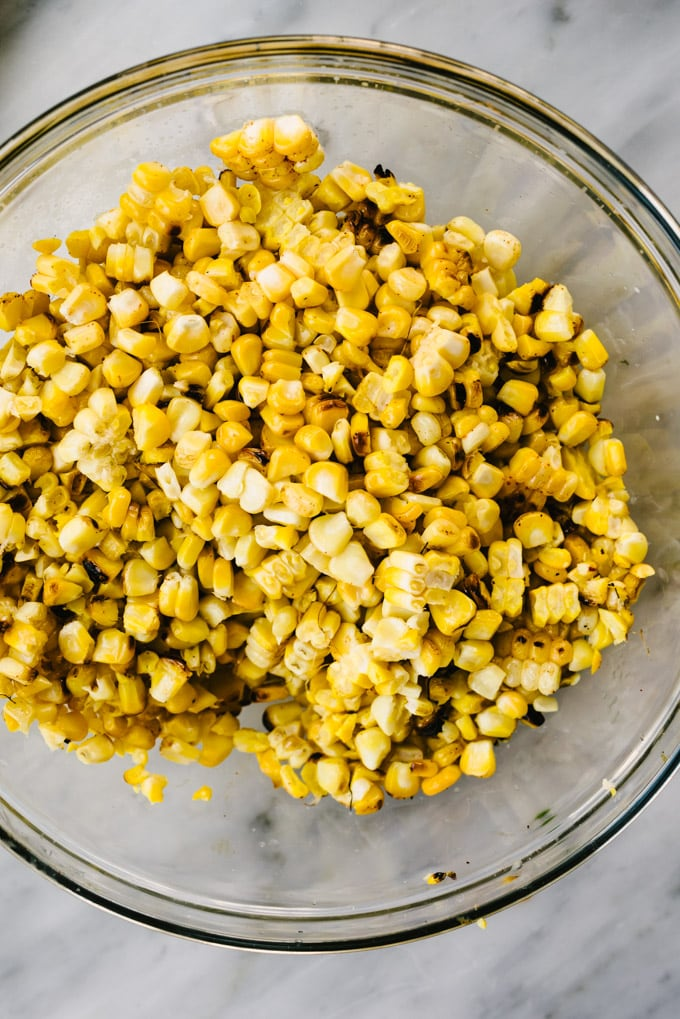 A bowl of fresh grilled corn kernels sliced from the cob on a marble table.
