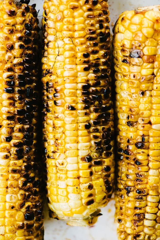 Three ears of charred and grilled sweet corn.