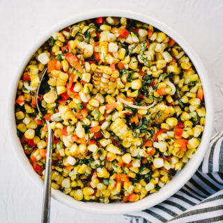 A bowl of simple grilled corn salad with lime, bell pepper, green onions, and basil on a marble table.