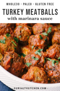 Paleo and whole30 turkey meatballs smothered with marinara sauce in a white serving bowl.