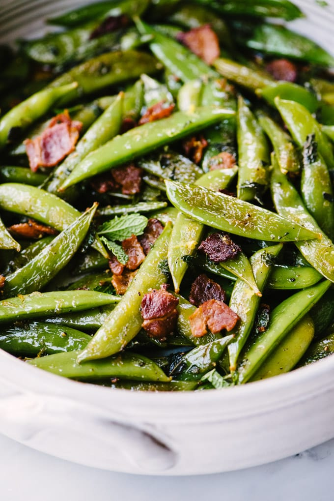 My favorite snap peas recipe! Sugar snap peas quickly sautéed with bacon and seasoned with fresh mint, lemon juice, and lemon zest.