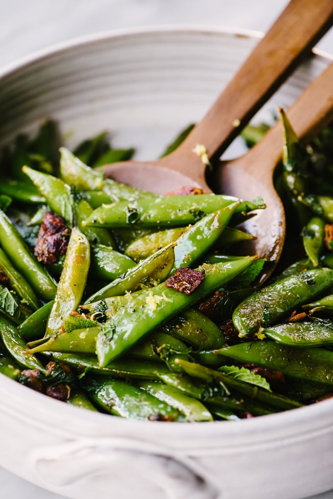 A large serving bowl of sugar snap peas sautéed with bacon and mint.