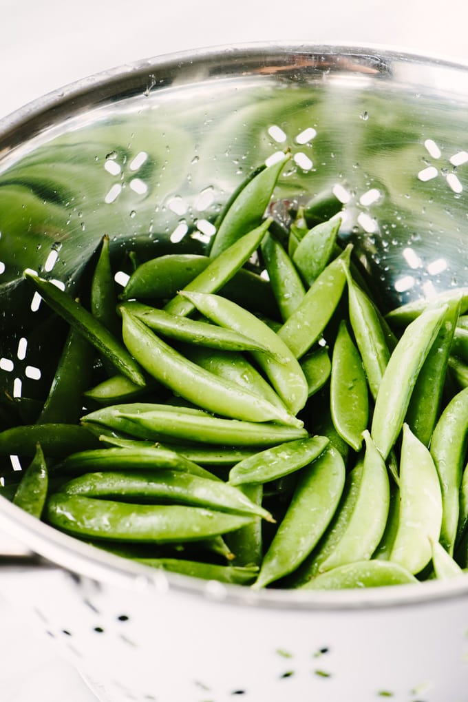 Raw sugar snap peas in white colander.