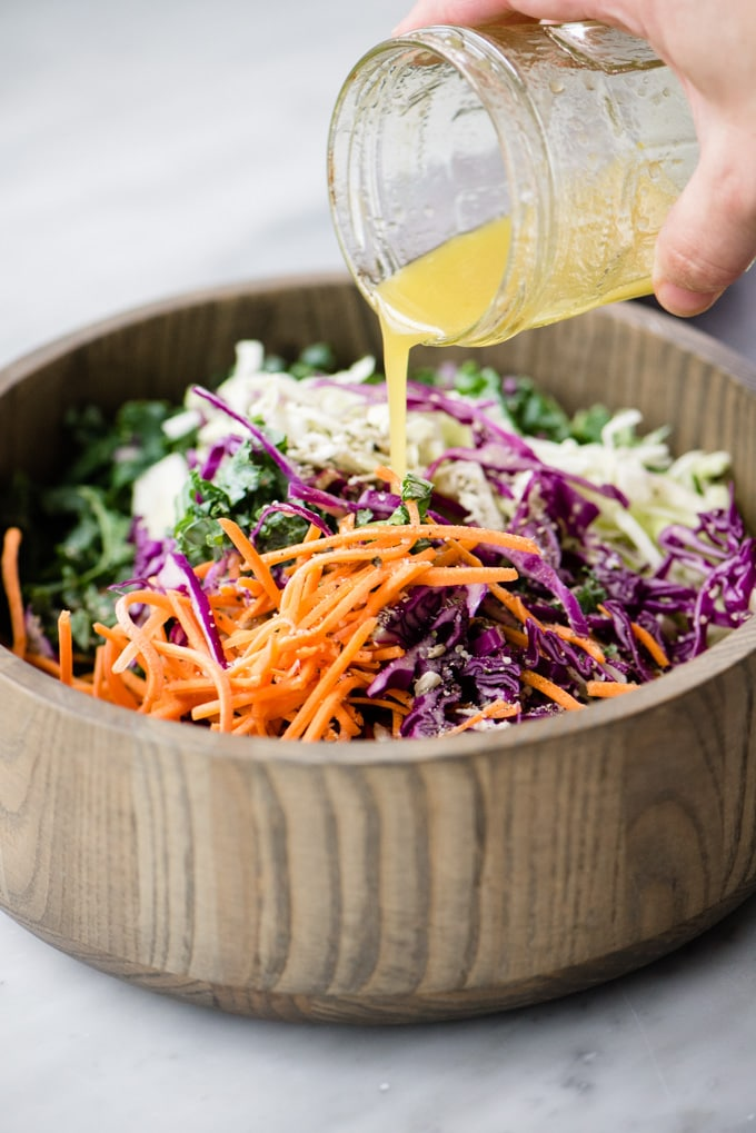 Adding apple cider dressing to a bowl of kale slaw.