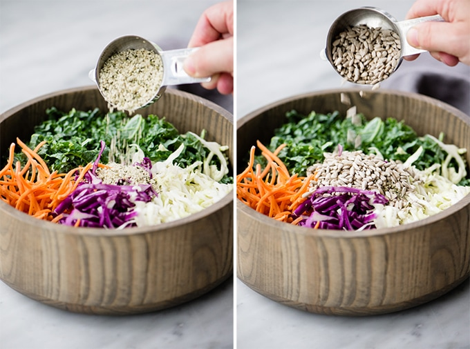 A woman's hand adding hemp seeds then sunflower seeds to crunchy kale slaw.