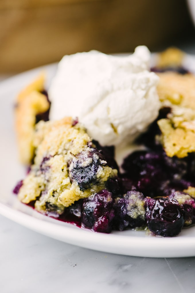 A heaping serving of skillet blueberry cobbler topped with homemade whipped cream.