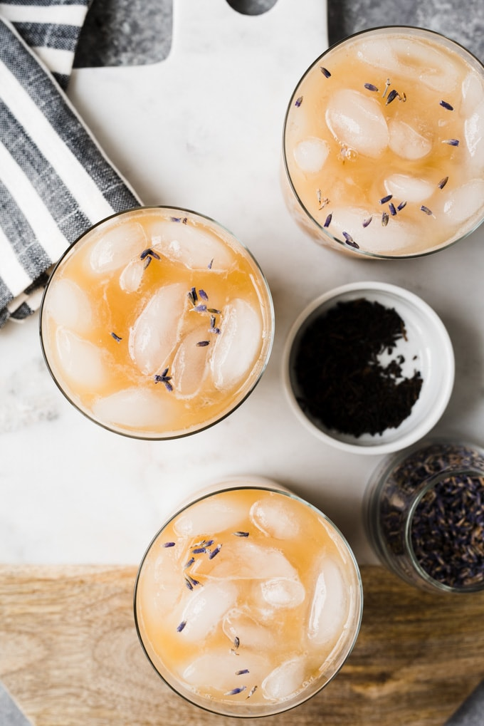 Three iced london fog tea lattes on a marble cutting board with a striped napkin and small jars of dried lavender and earl grey tea leaves.