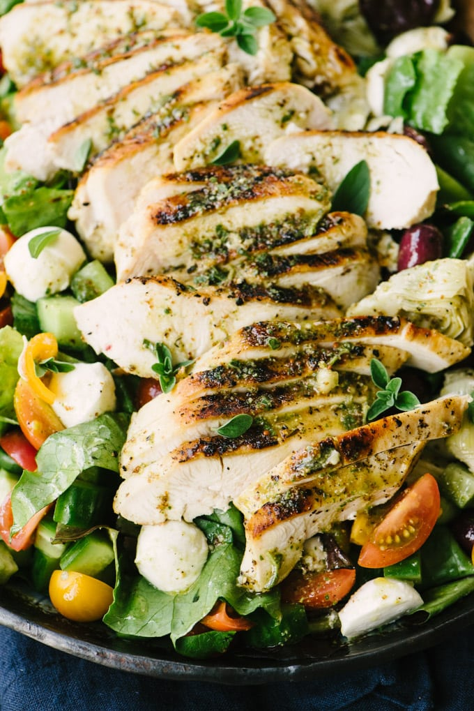 A detail image of grilled lemon oregano brined chicken atop a mediterranean chicken salad.