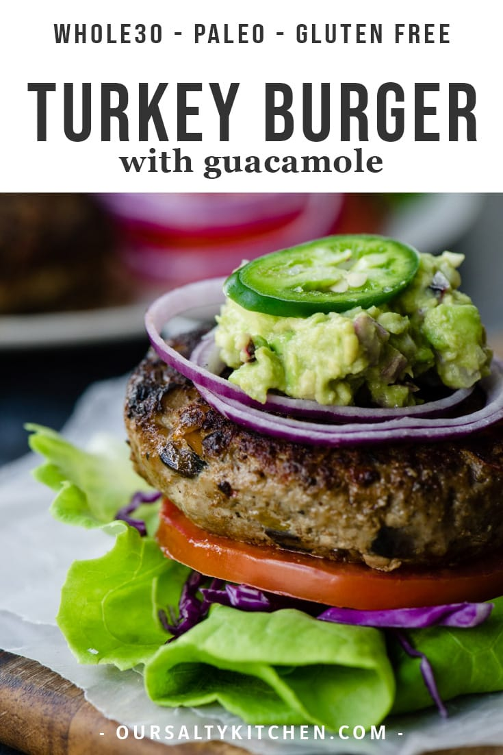 A veggie-packed paleo turkey burger on a lettuce bun with tomato, red onion, and guacamole.