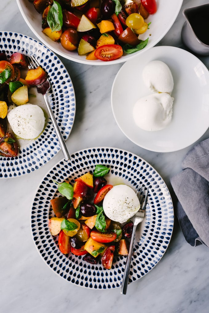Two plates of stone fruit salad with tomatoes and burrata cheese on a marble table.