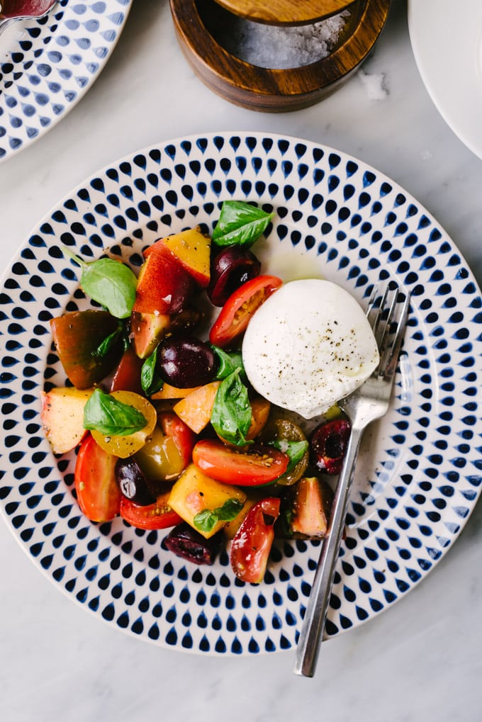 A serving of stone fruit salad with tomatoes and burrata cheese on a blue and white plate.