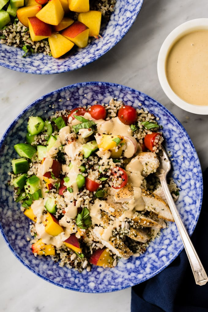 A blue bowl bursting with a healthy and protein packed summer quinoa salad drizzled with nut free sunbutter dressing.