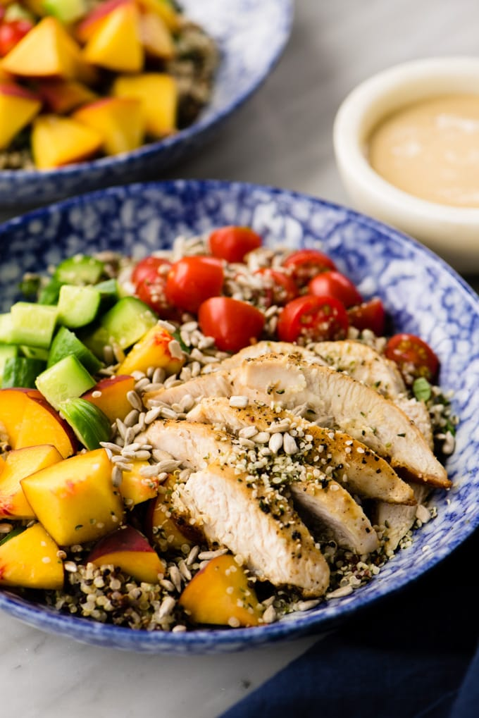 Light and refreshing summer quinoa salad with chicken, summer vegetables, and creamy sunbutter sauce.