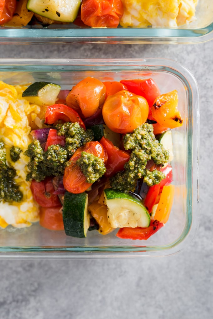 A veggie scramble meal prep bowl with roasted zucchini, bell peppers, and tomatoes and scrambled eggs drizzled with paleo pesto sauce.