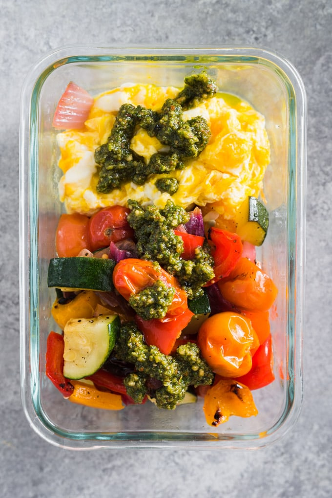 Veggie scramble breakfast prep bowl with roasted vegetables, scrambled eggs, and paleo pesto.