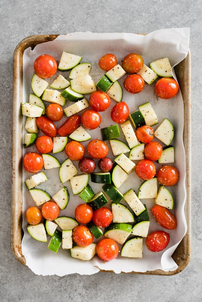 Diced zucchini and cherry tomatoes on a baking sheet ready to be roasted for veggie scramble meal prep bowls.