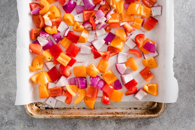 Red onion and bell pepper on a baking sheet ready to be roasted for veggie scrambled meal prep bowls.