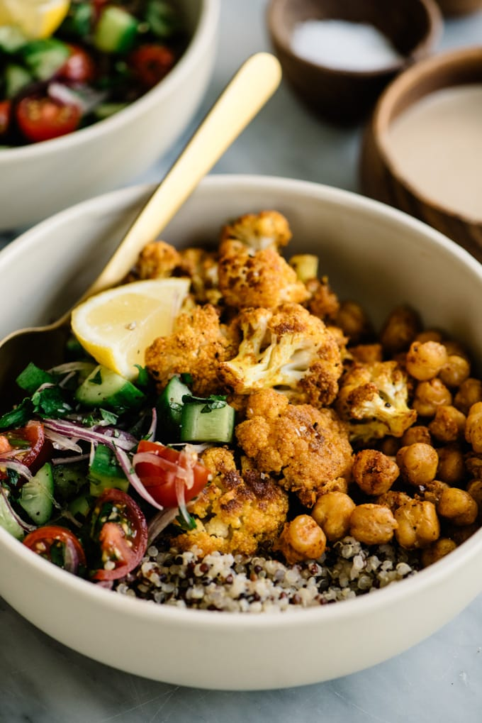 Roasted cauliflower shawarma with roasted crispy chickpeas, tomato salad, and quinoa in a cream bowl on a marble table.