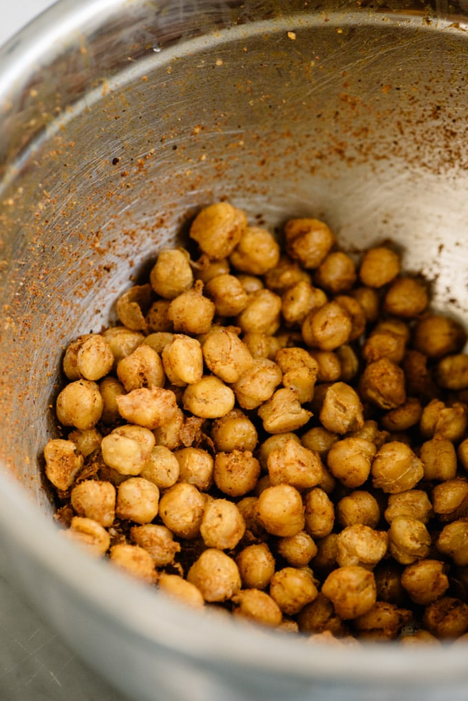 Chickpeas tossed with shawarma seasoning in a metal bowl.