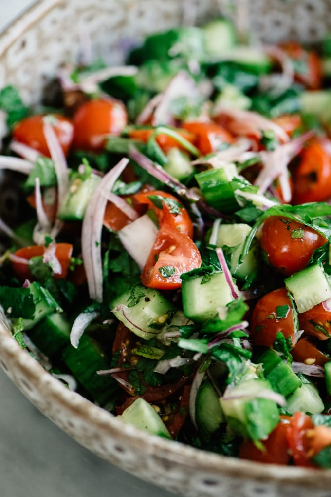 Tomato and cucumber salad in a brown ceramic bowl for vegan shawarma salad.