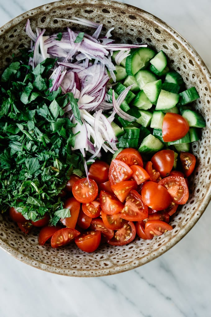 Cucumbers, tomatoes, sliced red onion, mint, and parsley in a brown ceramic bowl for a vegan shawarma salad.
