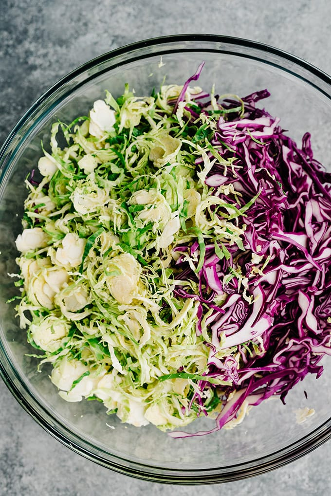 Shredded cabbage and shredded brussels sprouts in a large glass mixing bowl.