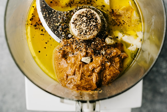Almond butter dressing ingredients in the bowl of a food processor.