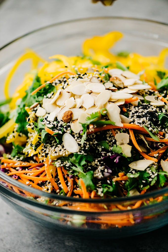 A glass mixing bowl filled with sliced vegetables, sesame seeds, and sliced almonds for a no mayo healthy chicken salad recipe.