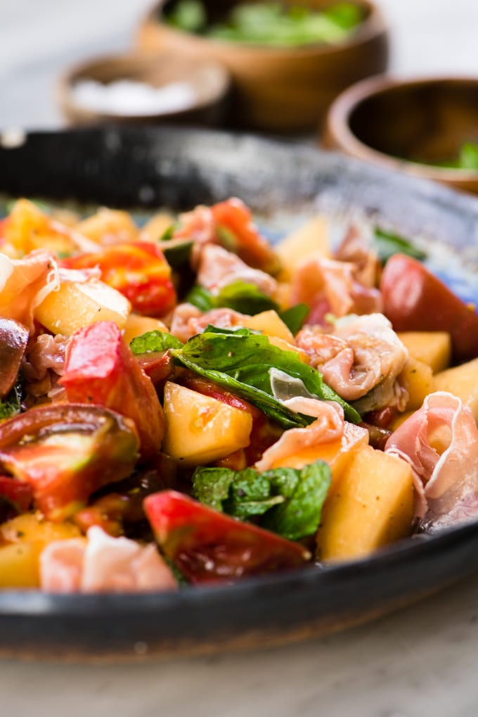 Melon salad with mint, basil, tomato and prosciutto in a blue salad bowl.