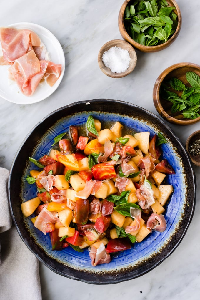 Summer melon salad with prosciutto, tomato, mint, and basil tossed with apple cider vinaigrette in a blue salad bowl on a marble table.