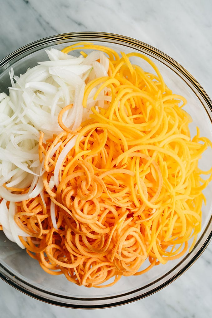 Spiralized sweet potatoes and butternut squash with thinly sliced sweet onion in a glass mixing bowl.